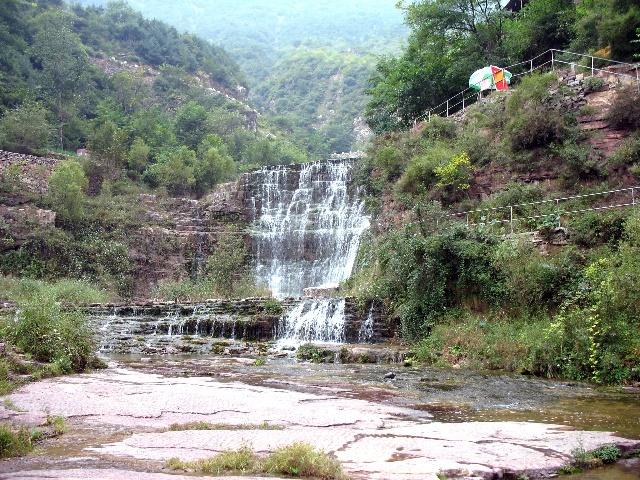 """在桃花谷中,200米内有大的跌水九处,形成九道瀑布,称为""""九连瀑""""。而实际上这200米内不只有九处,如果把小跌水也算在内,有十几处。因此,有人说这里的""""九""""是形容多的意思。就是有很多瀑布相连,而连成的景观。   九连瀑,潺潺流水,岩层可数,尤为壮观,特别是在天晴日丽的上午8点至10点,站在桃花瀑崖头向下观看,瀑雾中能现出七色长虹,美丽宜人,   九连瀑又被称为""""小黄果树瀑布"""",拍出来的照片,它的形状、气势都和贵州黄果树大瀑布非常相似。如果您有兴"""